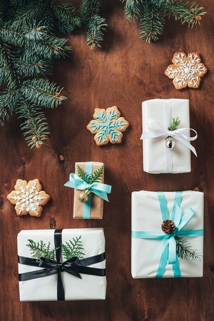 flat lay with christmas gift boxes with fir tree branches and cookies on wooden background