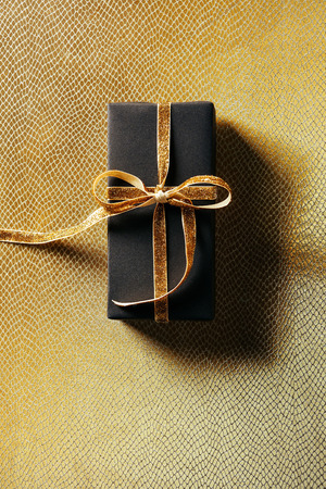 top view of wrapped gift box with golden ribbon on golden background 版權商用圖片