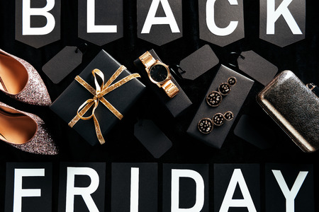 flat lay with feminine shoes, jewelry and purse with blank price tags on black background, black friday concept