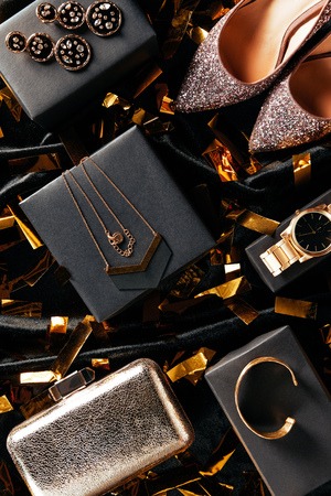 flat lay with feminine shoes, purse and jewelry on black background with golden confetti Stock Photo
