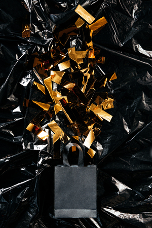Top view of paper shopping bag with golden confetti on black wrapping paper backdrop, black Friday concept 免版税图像