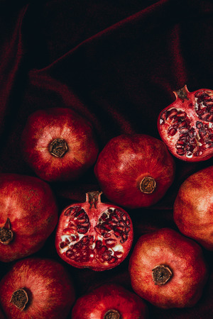 Top view of arranged pomegranates on red velvet fabric background