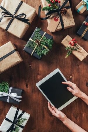 Cropped view of woman using digital tablet with blank screen on wooden background with Christmas presents