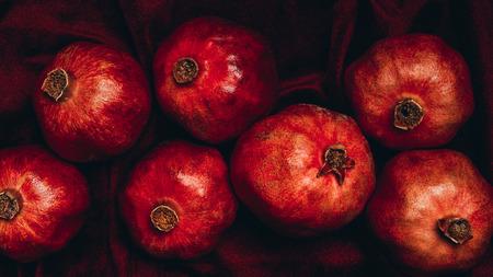 Flat lay with fresh pomegranates on red velvet cloth backdrop Stock Photo