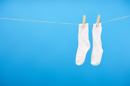 Close-up view of clean white socks hanging on rope isolated on blue