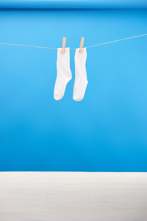 clean white socks hanging on clothesline on blue 스톡 콘텐츠
