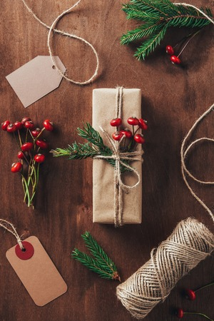 flat lay with christmas gift fir branches, decorative berries, twine and tags on wooden background