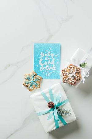 Top view of white Christmas gifts, snowflake cookies and greeting card with baby its cold outside lettering on marble table