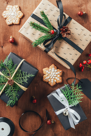 Flat lay with presents, Christmas balls, fir branches and cookies on wooden background
