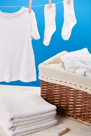 Close-up view of laundry basket, pile of clean soft towels and white clothes hanging on clothesline on blue