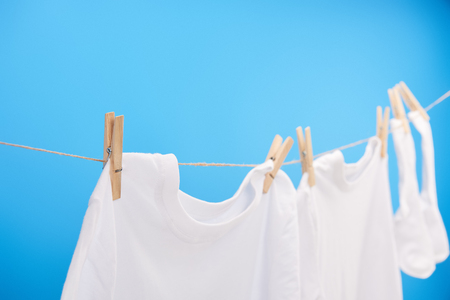 close-up view of clean white t-shirts and socks hanging on clothesline isolated on blue