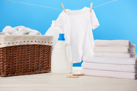 plastic containers with laundry liquids, laundry basket, pile of towels and clean white clothes hanging on rope on blue Stock Photo