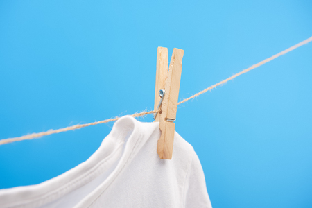Close-up view of clean white t-shirt with clothespin hanging on rope isolated on blue