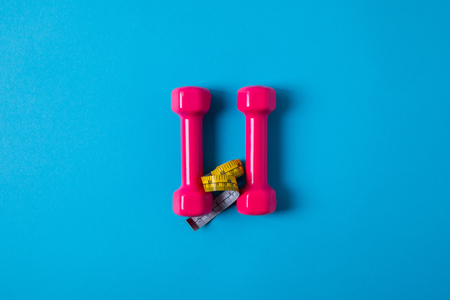 View from above of yellow measuring tape and pink dumbbells isolated on blue, minimalist concept Stock Photo - 112270477