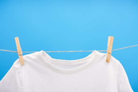 Close-up view of clean white t-shirt with clothespins hanging on rope isolated on blue
