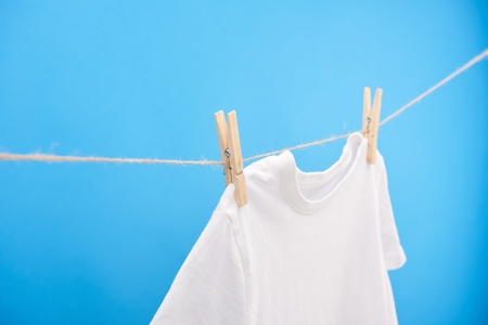 Clean white t-shirt with clothespins hanging on rope isolated on blue Reklamní fotografie