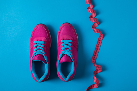 View from above of pink sport shoes and measuring tape isolated on blue, minimalist concept Stock Photo