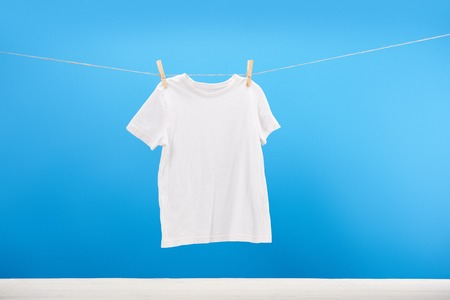 Clean white t-shirt hanging on clothesline on blue Archivio Fotografico - 112270565