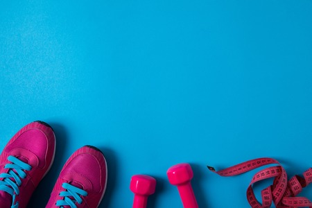 elevated view of pink sneakers, dumbbells and measuring tape placed in row isolated on blue Stock Photo