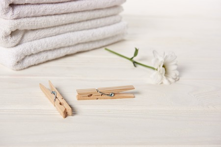 close-up view of clothespins, beautiful chamomile flower and clean soft towels on white wooden table Archivio Fotografico - 112155550