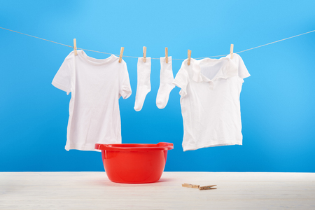 red basin, clothespins and clean white clothes hanging on rope on blue Archivio Fotografico - 112155556