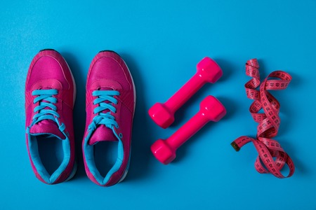 flat lay with arranged pink sneakers, dumbbells and measuring tape placed in row isolated on blue, minimalistic concept