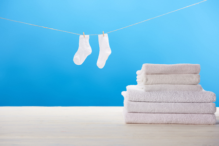 pile of soft towels and clean white socks hanging on clothesline on blue background
