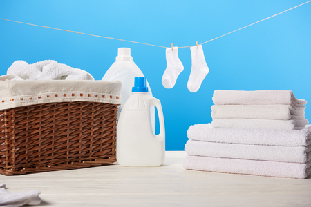 laundry basket, plastic containers with laundry liquids, pile of clean soft towels and white socks hanging on rope on blue