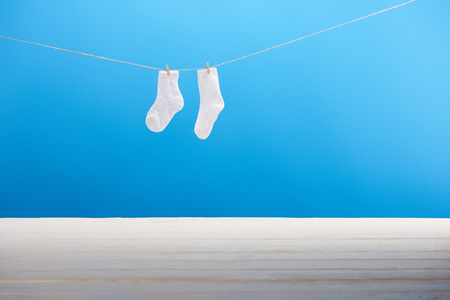 Clean white socks hanging on clothesline on blue background