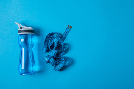Top view of sport bottle and measuring tape isolated on blue, minimalist concept