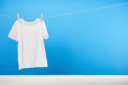 Sauberes weißes T-Shirt, das an einem Seil auf Blau hängt