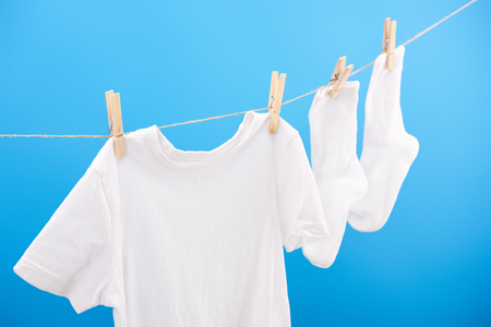 Clean white socks and t-shirt hanging on clothesline isolated on blue Archivio Fotografico - 112270573