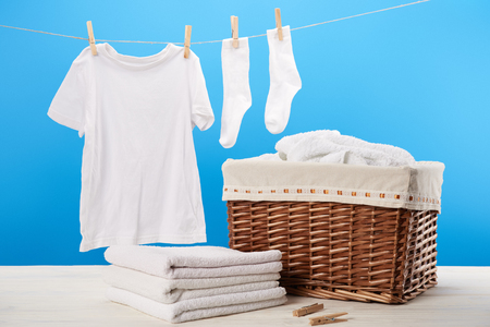 Laundry basket, pile of clean soft towels and white clothes hanging on clothesline on blue 版權商用圖片 - 112270581