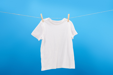 White t-shirt with clothespins hanging on clothesline isolated on blue Archivio Fotografico - 112270541