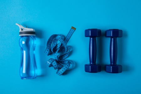 View from above of sport bottle with water, measuring tape and dumbbells isolated on blue Stock Photo