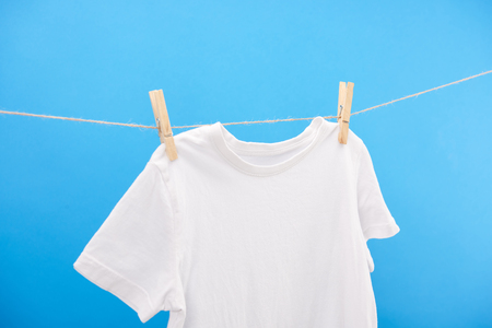 close-up view of clean white t-shirt hanging on clothesline isolated on blue