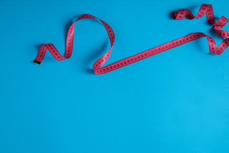 top view of pink measuring tape isolated on blue, minimalistic concept Stock Photo