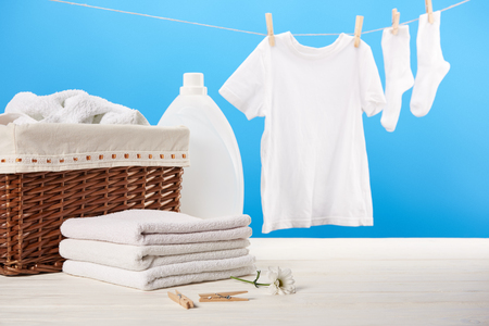 laundry basket, plastic container with laundry liquid, pile of clean soft towels and white clothes hanging on clothesline on blue Stock Photo