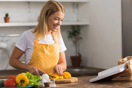 smiling young woman in apron cutting vegetables and reading cookbook in kitchen