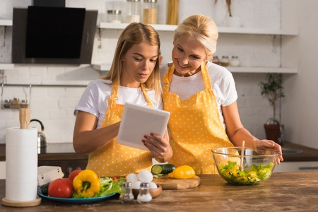 adult mother and daughter in aprons using digital tablet while cooking together Stock Photo