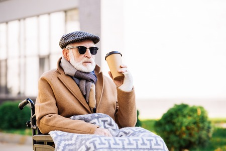 senior disabled man in wheelchair holding paper cup of coffee on street