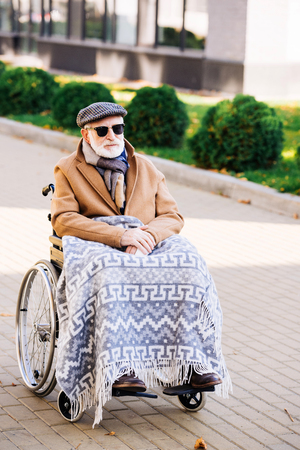 Senior disabled man in wheelchair with plaid on legs on street