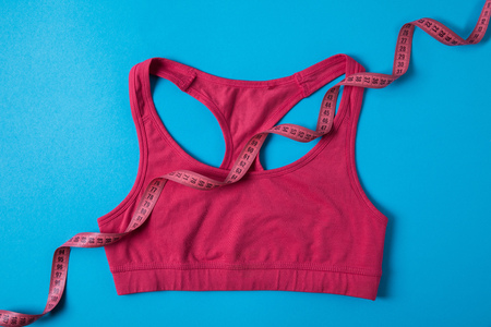 Elevated view of pink sports bra and measuring tape isolated on blue, minimalist concept Stock Photo - 112270638