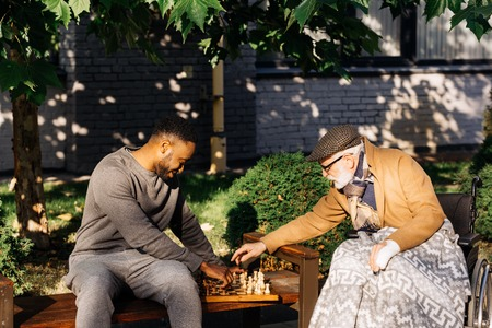 Senior disabled man in wheelchair and African american nurse playing chess together on street Stok Fotoğraf