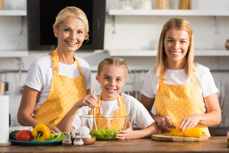 Adorable happy child with mother and grandmother smiling at camera while cooking together
