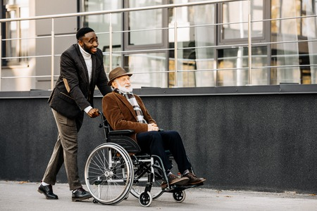 Happy senior disabled man in wheelchair and African american cuidador riding by street Foto de archivo - 112270623