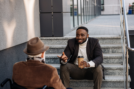 Senior disabled man in wheelchair and African american man drinking coffee together and chatting on street