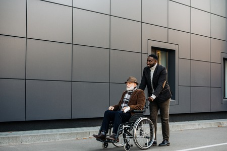 Senior disabled man in wheelchair and young African american cuidador riding by street