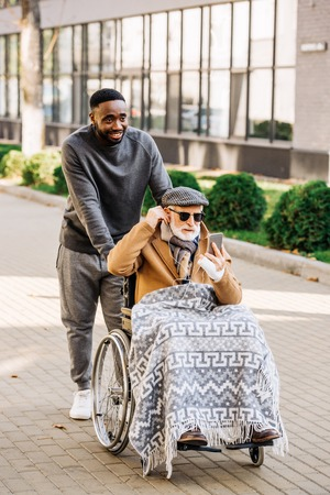 senior disabled man in wheelchair listening musing with smartphone and earphones with african american cuidador on street Stock Photo