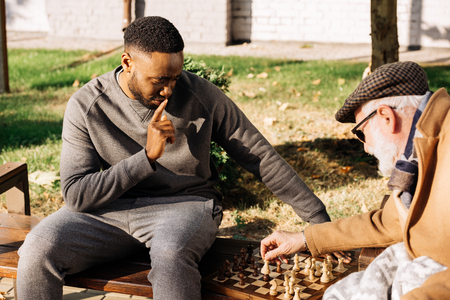 senior man and thoughtful african american man playing chess together on street